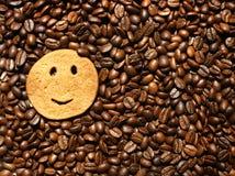 Cookie de sorriso no fundo dos feijões de café imagem de stock royalty free