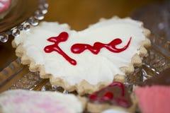 Cookie do coração do Valentim com o amor da palavra escrito no frostin vermelho Fotos de Stock Royalty Free
