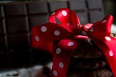 Cookie dos pedaços de chocolate com barra de chocolate e curva de seda vermelha com pontos brancos fotos de stock royalty free