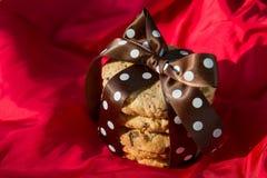 Cookie dos pedaços de chocolate com curva de seda marrom e pontos brancos em um fundo de seda vermelho fotos de stock royalty free
