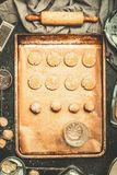 Cookie dough on baking tray with kitchen baking tolls and ingredients Stock Images