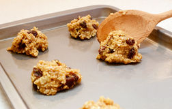 Cookie dough being spooned onto baking sheet. Oatmeal raisin cookie dough spooned onto baking sheet with selective focus Stock Image