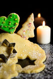 Cookie dough and cookies, candle and icing sugar in front of a b Royalty Free Stock Images