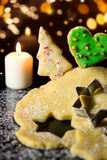 Cookie dough and cookies, candle and icing sugar in front of a s Royalty Free Stock Image