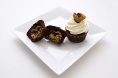 Cookie dough cupcake. One open cupcake showing the cookie dough, one cupcake with white frosting and a cookie piece as decoration Stock Photography