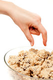 Cookie Dough Eat. A hand reaching for a bowl of raw cookie dough Royalty Free Stock Image