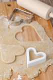 Cookie dough rolled out with heart shapes cut into it Stock Images