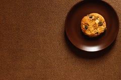 A cookie encontra-se em uma placa em um fundo marrom Imagem de Stock Royalty Free