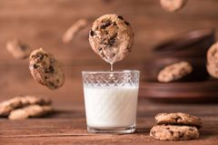 Cookie falls into the glass of milk. Stock Photo