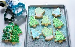 Cookie festiva do Natal dada forma como mitenes e árvores na bandeja do cozimento Foto de Stock