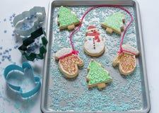 Cookie festiva do Natal dada forma como o boneco de neve e as árvores na bandeja do cozimento Foto de Stock