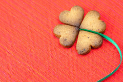 Cookie in the form of an Irish clover. And green on a red background royalty free stock photo