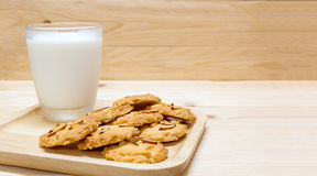 Cookie. Fresh homemade almond cookies with glass of milk on wooden tray and wooden background Stock Photos