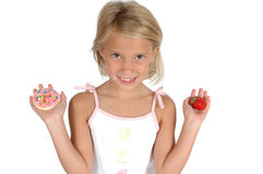 Cookie or Fruit?. A child has to choose between eating a cookie or a strawberry fruit. Teaching children about healthier diets. Child on white background Stock Images