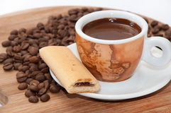 Cookie with fruit filling and a cup of coffee with raw coffee be Stock Photos