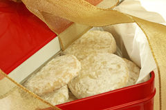 Cookie Gift Tin. Red gift tin full of shortbread cookies; gold mesh bow/ribbon Stock Images