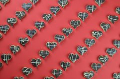 Cookie hearts in rows on red. Diagonal rows out of home made heart shaped cookies with chocolate on red background Royalty Free Stock Photos