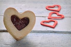 Cookie with jam and three red paper hearts Royalty Free Stock Photos