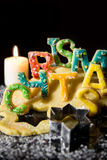 Cookie letters with cookie dough and a candle, word Christmas in Stock Photo
