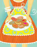 Cookie mama. A loving mother in a red dress and an apron, holding a plate of delicious, home-baked cookies Royalty Free Stock Image