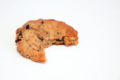 Cookie with missing bite. Close up of a raisin oatmeal cookie with a big bite taken out of it on a white background, isolated royalty free stock image