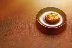Cookie, placa e fundo marrom Foto de Stock