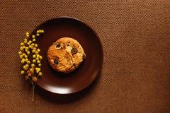 Cookie, placa, fundo marrom e flor Fotos de Stock Royalty Free