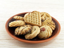 close up pile of assorted biscuit cookies (heart shape on top) on brown ceramic baked clay dish on wooden kitchen table royalty free stock image