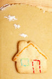 Cookie in shape of house. On dough with flour as clouds Royalty Free Stock Images