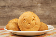 Cookie with a smile. On a plate on wooden background texture Stock Photo