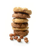 Cookie Stack. Studio macro of freshly made stack of warm chocolate chip cookies with scattered hazelnuts on a white surface with soft shadows. Copy space stock photography