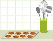 Cookie tray on counter. Tray of chocolate chip cookies on a counter with a plate stack and a container of cooking utensils stock illustration