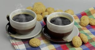 Cookie and two cups of coffee. Kruidnoten, pepernoten, strooigoed. Cookie and two cups of coffee. Kruidnoten, pepernoten, traditional sweets, strooigoed stock video