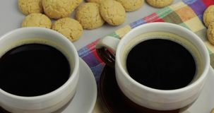 Cookie and two cups of coffee. Kruidnoten, pepernoten, strooigoed. Cookie and two cups of coffee. Kruidnoten, pepernoten, traditional sweets, strooigoed stock video footage