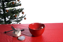 Cookie Utensiles. A mixing bowl, wisk, jar of flour and assorted kitchen utensiles on a table in front of a Christmas tree ready for someone to come along and Royalty Free Stock Image