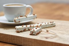 Cookie wafers in glaze and cup of coffee on a wooden table stock image