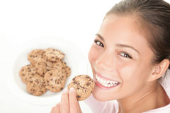 Cookie woman. Eating chocolate chip cookies. Cute young mixed race chinese / caucasian model on white background Stock Images