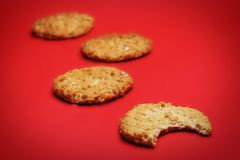 Cookies. On a red background, one with a bite out of it stock images