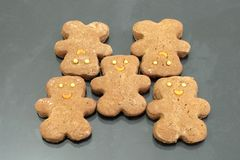 Cookies. Ginger bear cookies with golden ball eyes and orange sickle smile Royalty Free Stock Image