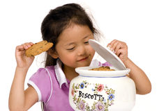 Cookies. A young girl takes a cookie from the Jar Royalty Free Stock Photography