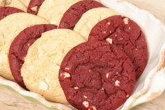 Cookies. Red velvet and white chocolate macadamia cookies in a ceramic bowl with a wooden tabletop background. Selective focus with shallow DOF Stock Images