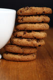 Cookies. A stack of chocolate chip cookies against a white cup royalty free stock images