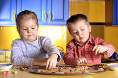 Cookies. Young girl and little boy create cookies Stock Photos