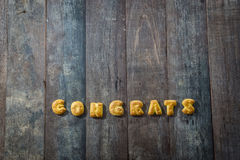 Cookies ABC in the form of word CONGRATS. Alphabet on old wood background stock photography