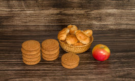 Cookies, apple and croissants. On a wooden background Royalty Free Stock Image
