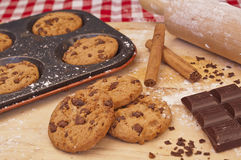 Cookies on a baking tray. Baked chocolate chip cookies on a baking tray with cinnamon, chocolate and a rolling pin in the background royalty free stock images