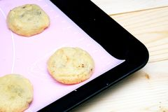 Cookies in baking tray. On the table Wood Royalty Free Stock Photography