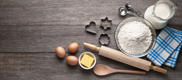 Cookies Baking Wood Ingredients Background. Various baking ingredients and cookie utensils on a rustic wood banner background Royalty Free Stock Photos