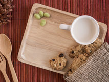 Cookies and bean with cup of milk in the wooden tray Royalty Free Stock Image