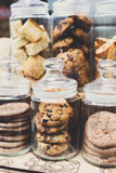 Cookies and biscuits in glass jars on bar for sale. Desserts choice. Cookies and biscuits in glass jars on counter bar for sale. Chocolate drops and chips Stock Photography